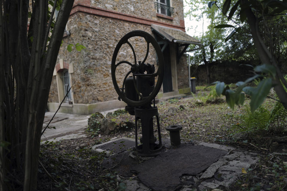 """The manual pump of a water well in the garden of the 120 sq. meters (1,300 sq. feet) stone house where the Nobel-winning scientist couple Marie Sklodowska-Curie and Pierre Curie spent vacation and weekends from 1904-1906 in Saint-Remy-les-Chevreuse, on the south-west outskirts of Paris, France, Wednesday, May 12, 2021. Poland's prime minister Mateusz Morawiecki says he's given instructions for the government to buy 790,000 euro house in France, and said on Twitter Tuesday that the house, is a """"part of Poland's history."""" (AP Photo/Francois Mori)"""