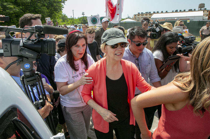 Democratic presidential candidate Sen. Elizabeth Warren, D-Mass., is swarmed by the media while walking past the Homestead Detention Center, where the U.S. is detaining migrant teens, in Homestead, Fla., Wednesday June 26, 2019. (Daniel A. Varela/Miami Herald via AP)