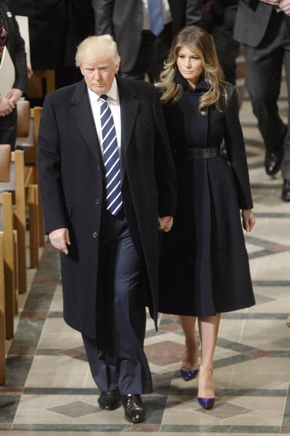 <p>The day after her husband's inauguration, Melania Trump traded her white gown designed by Hervé Pierre for a black wool coat from Alice Roi. (Photo: AKM-GSI) </p>