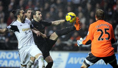 Swansea City's Chico Flores (L) challenges Manchester City's Alvaro Negredo (C) during their English Premier League soccer match at the Liberty Stadium in Swansea, Wales, January 1, 2014. REUTERS/Rebecca Naden