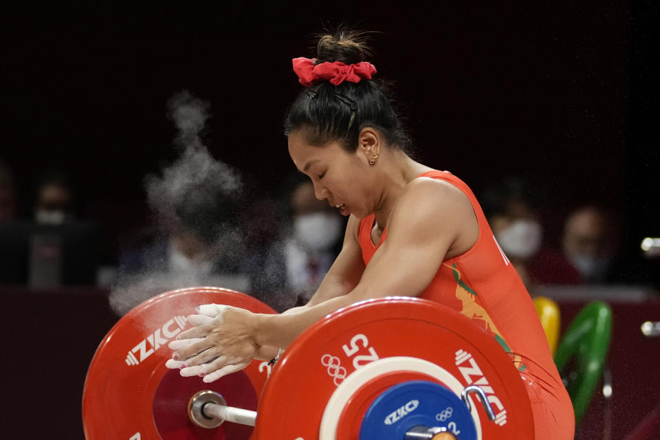 Mirabai Chanu Saikhom of India reacts to an unsuccessful attempt as she competes in the women's 49kg weightlifting event, at the 2020 Summer Olympics, Saturday, July 24, 2021, in Tokyo, Japan. (AP Photo/Luca Bruno)