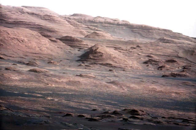 <p>The base of Mars's Mount Sharp — the rover's eventual science destination — is pictured in this NASA handout photo taken by the Curiosity rover. The image is a portion of a larger image taken by Curiosity's 100-millimeter Mast Camera on Aug. 23, 2012. Scientists enhanced the color to show the Martian scene under the lighting conditions we have on Earth, which helps in analyzing the terrain. (Photo: NASA/Reuters) </p>