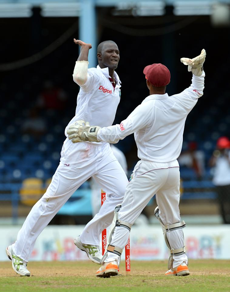 West Indies cricketer Darren Sammy (L) and Carlton Baugh (R) celebrate the wicket of Australian batsman Michael Clarke during the final day of the second-of-three Test matches between Australia and West Indies April19, 2012 at Queen's Park Oval in Port of Spain, Trinidad.