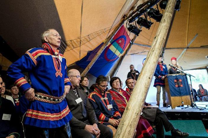 Per Mikael Utsi, standing, member of the Sami Parliament, takes part in the opening session of the parliament in Jokkmokk, northern Sweden, on Thursday Aug. 28, 2013. The Swedish Sami Parliament this year celebrates its 20th anniversary. Since the end of the last Ice Age, the Sami have wandered the vast landscapes of northern Europe, herding reindeer and nurturing a philosophy of harmony with nature (AP Photo/Carl-Johan Utsi) SWEDEN OUT