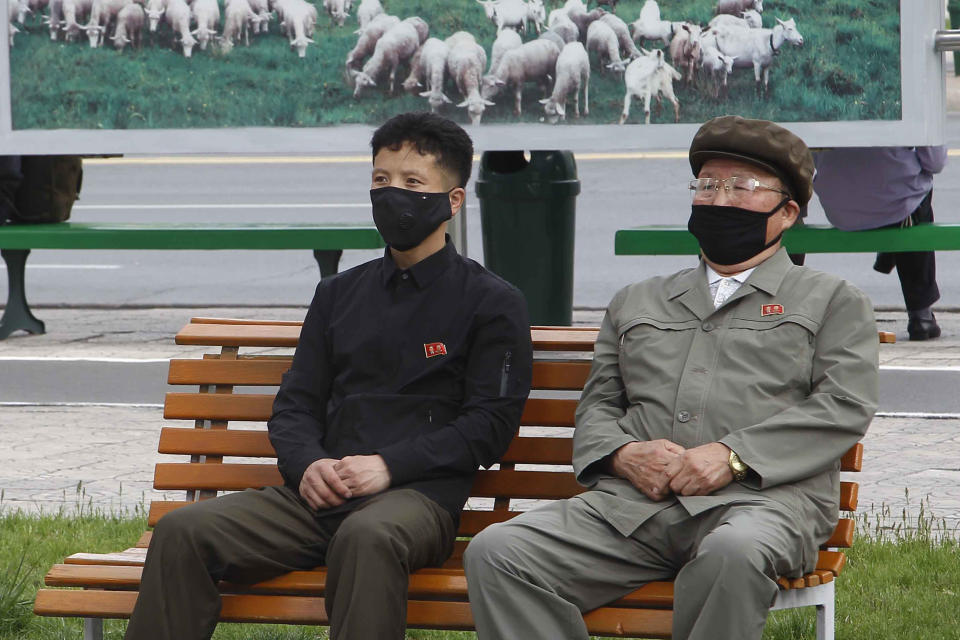 People in a park wearing masks watch news broadcasted on a giant screen showing leader Kim Jong Un attending the opening ceremony of the Sunchon Phosphatic Fertilizer Factory Saturday, May, 2nd. 2020, in Pyongyang, North Korea. Un made his first public appearance in 20 days as he celebrated the completion of a fertilizer factory near Pyongyang, state media said Saturday, ending an absence that had triggered global rumors that he may be seriously ill. (AP Photo/Jon Chol Jin)
