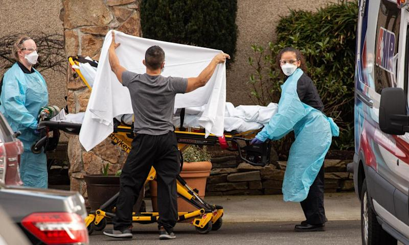 Healthcare workers transport a patient on a stretcher into an ambulance at Life Care Center of Kirkland in Kirkland, Washington on February 29th.