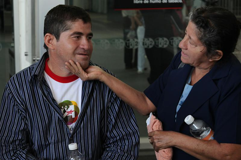Sea survivor Jose Salvador Alvarenga looks at his mother Maria Julia, as she cups his chin in her hand, during an interview, after arriving at the airport in Mexico City, Friday, March 14, 2014. The Salvadoran fisherman, who was lost at sea for 13 months, traveled from El Salvador to Mexico to fulfill a promise he made to his dead sea mate, Mexican Ezequiel Cordoba. Alvarenga said Cordoba died a month into their ordeal because he couldn't stomach the diet of raw fish, turtles and birds. (AP Photo/Marco Ugarte)