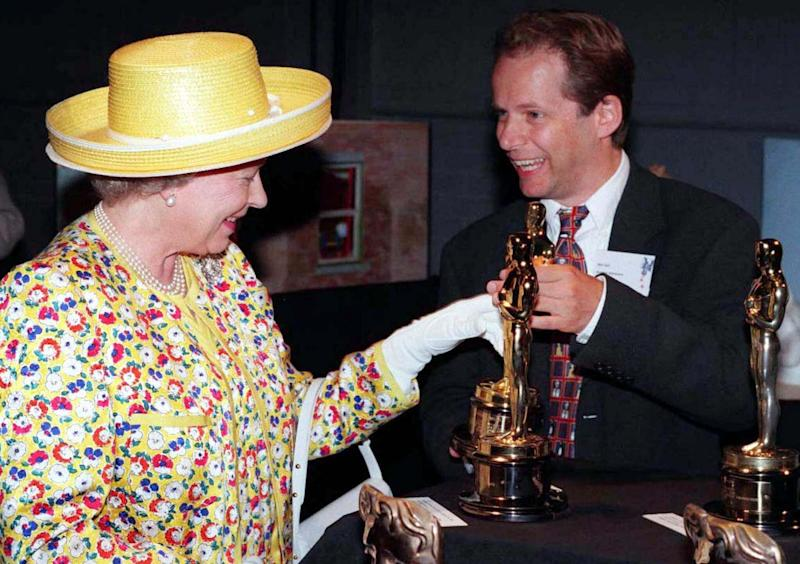 Queen Elizabeth II admires the Oscars given to film animator Nick Park during a visit to Aardman Animations in Bristol, July 19.