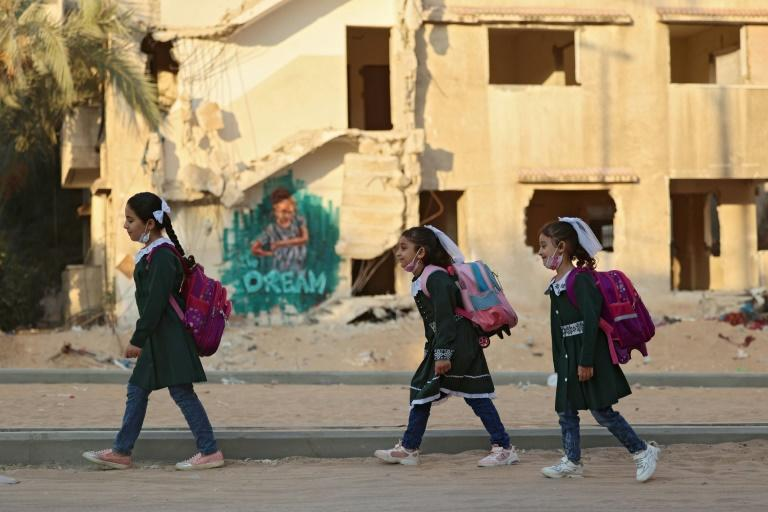 Palestinian children walk past a destroyed building on their way to school for the first day of the new scholastic year in Gaza City on August 16, 2021