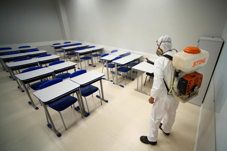 BRASILIA, BRAZIL - JULY 31: A sanitation worker wearing PPE disinfects a classroom of a public school  amidstthe coronavirus (COVID-19) pandemic at the Candangolância on July 21, 2020 in Brasilia. The government of the capital of Brazil intends to return to face-to-face classes in August as the country reports over 2.610,000 confirmed positive cases of Coronavirus and reports over 91,263 deaths. (Photo by Andressa Anholete/Getty Images)