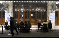 People take a drink outside a theatre on Saint Martin's Lane in central London, Saturday, Oct. 31, 2020. Earlier Saturday British Prime Minister Boris Johnson announced England will start a month long lockdown next week. Johnson says the new measures will begin Thursday and last until Dec. 2. (AP Photo/Alberto Pezzali, Pool)