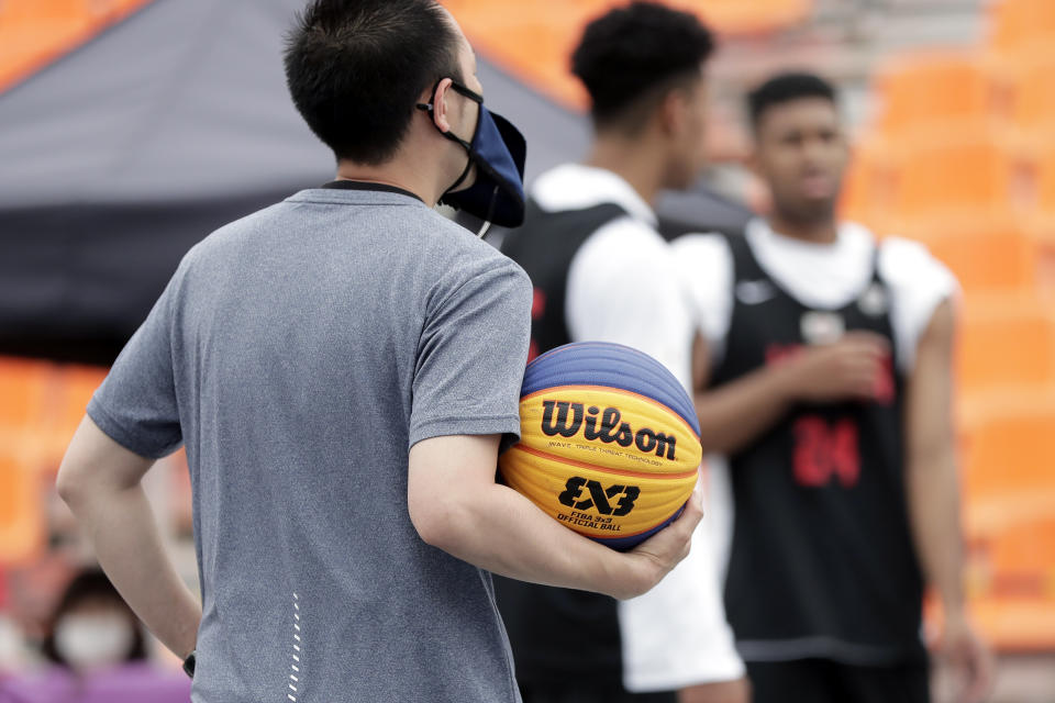 TOKYO, JAPAN - MAY 16: A referee wearing a mask holds a ball in the Men's semi-final match during the 3x3 Basketball Olympic test event at the Aomi Urban Sports Park on May 16, 2021 in Tokyo, Japan. (Photo by Kiyoshi Ota/Getty Images)
