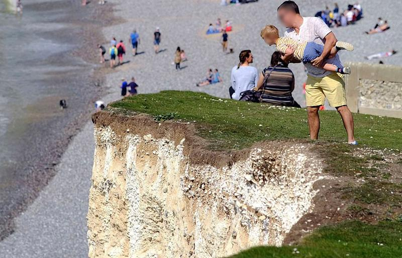 A father clutches his toddler close to the edge of the Seven Sisters cliffs in East Sussex, England.
