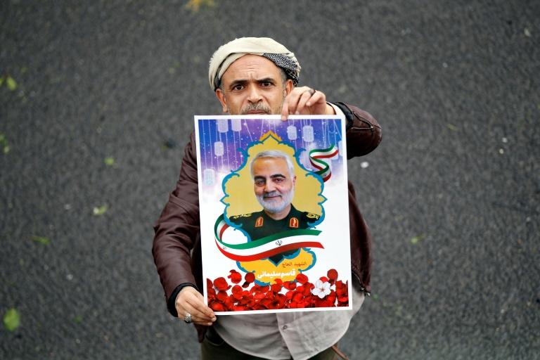 "A Yemeni supporter of the Iran-backed Huthi movement holds aloft a picture of slain Iranian general Qasem Soleimani who many across the Middle East have hailed as a ""living martyr"""