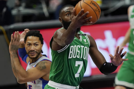 Boston Celtics guard Jaylen Brown (7) makes a layup as Detroit Pistons guard Derrick Rose defends during the first half of an NBA basketball game Friday, Jan. 1, 2021, in Detroit. (AP Photo/Carlos Osorio)