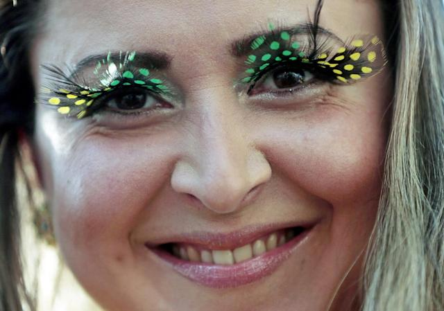 A spectator wears colorful eyelashes before the group A World Cup soccer match between Brazil and Croatia, the opening game of the tournament, in the Itaquerao Stadium in Sao Paulo, Brazil, Thursday, June 12, 2014. (AP Photo/Ivan Sekretarev)