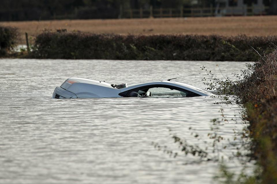 A car floats in floodwater near Fishlake in Doncaster. The Prime Minister is set to chair a meeting of the Government's emergency committee after severe flooding in parts of the country, where rain is finally expectedd to ease this afternoon.