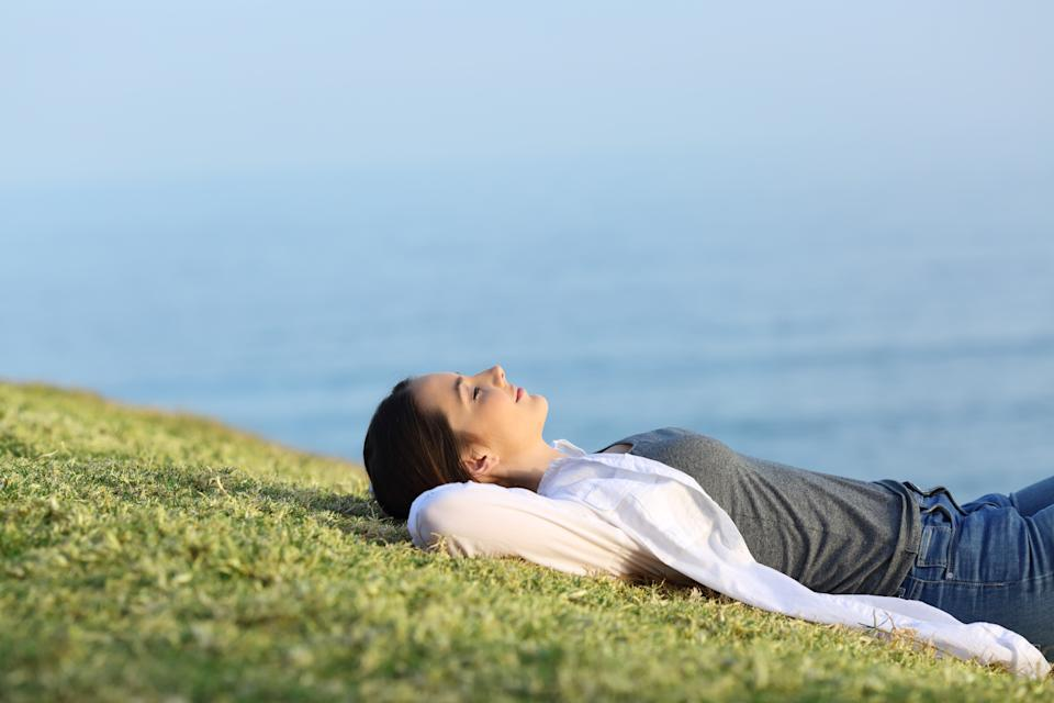 Side view portrait of a relaxed woman resting lying on the grass in the coast with the ocean in the background