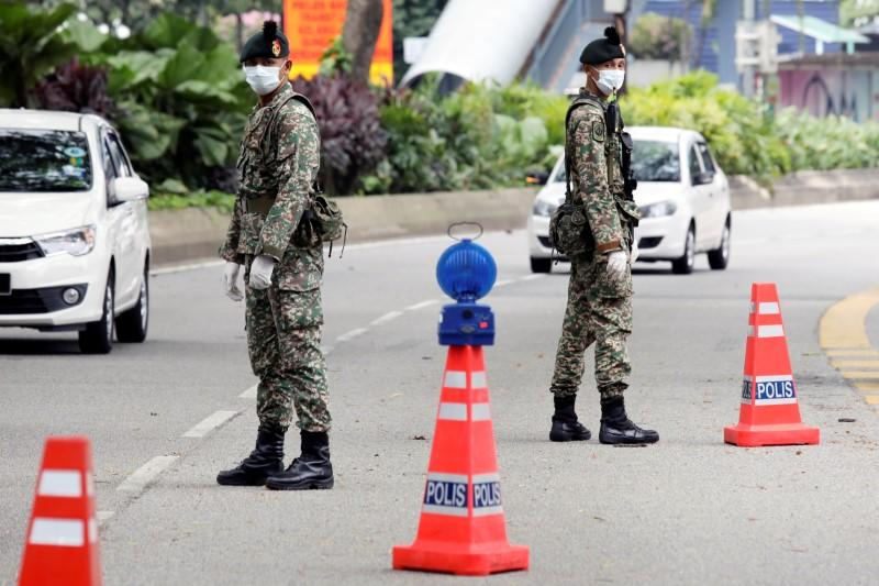 Soldiers wearing protective masks stand guard at a roadblock in Kuala Lumpur