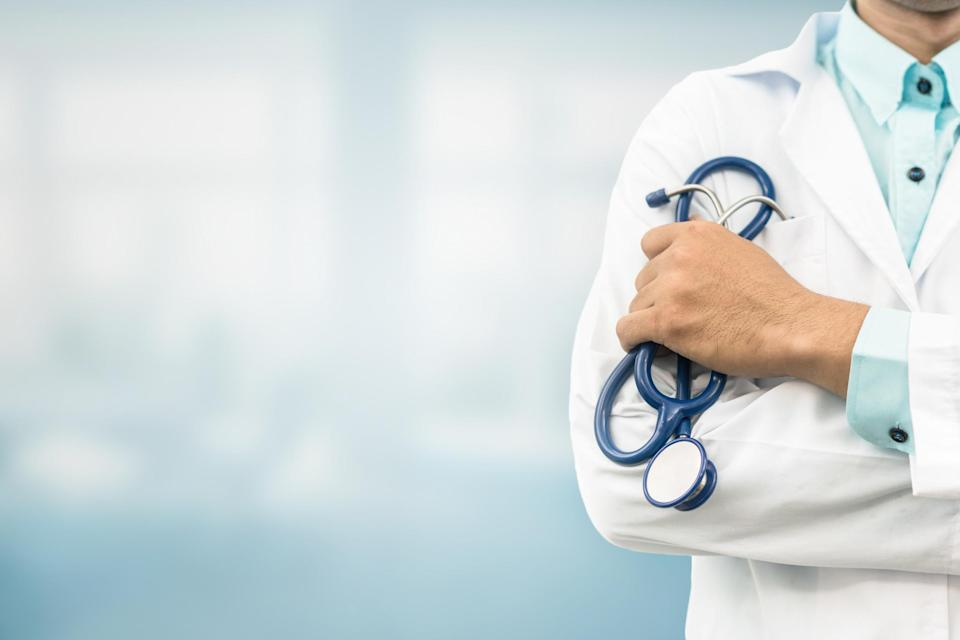 Person in white lab coat holding a stethoscope.