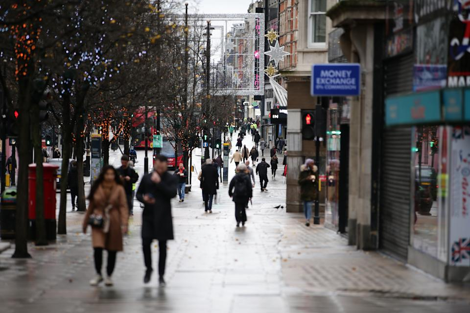People walk past temporarily-closed stores on Oxford Street in London, England, on December 21, 2020. London spent its second day of what could be months under newly-introduced 'Tier 4' coronavirus restrictions today. Under Tier 4 rules non-essential shops and many other businesses including gyms and hairdressers must close, with people instructed to stay at home other than for exempted circumstances including travel to work or education. Indoor mixing between those in different households is also banned under the new tier, upending Christmas plans for a huge swathe of the population. Concern over a more infectious strain of the coronavirus in the UK has meanwhile seen dozens of countries ban arrivals from Britain, with food supplies also disrupted after France closed the cross-Channel freight route from Dover. (Photo by David Cliff/NurPhoto via Getty Images)