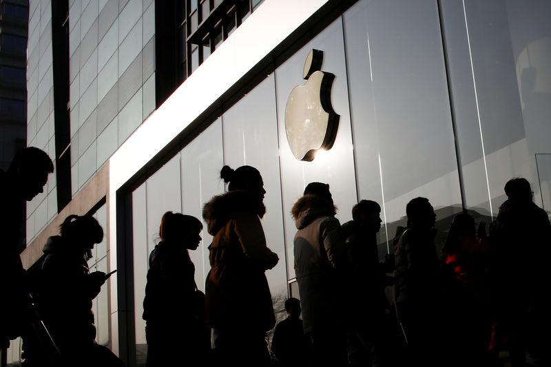 People line up at an Apple store shortly before it opens in Beijing