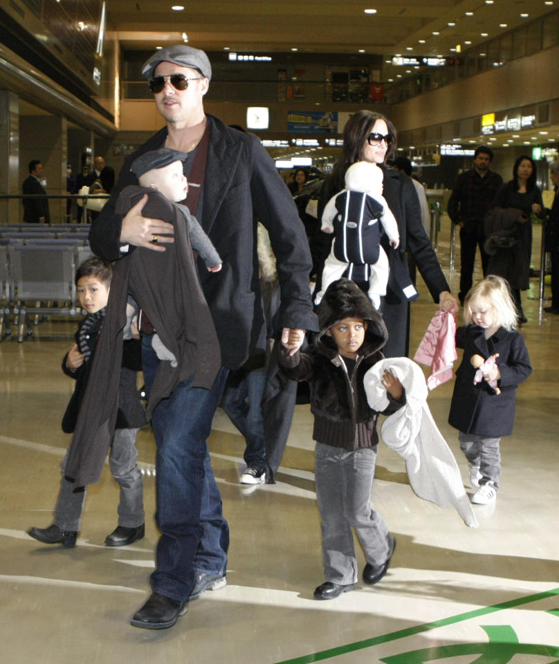 "U.S. actors Brad Pitt and Angelina Jolie arrive with their children at Narita airport, near Tokyo, January 27, 2009. Pitt is in Japan to promote the film ""The Curious Case of Benjamin Button"". From L-R: Pax, Knox Leon (carried by Pitt), Maddox (obscured), Zahara, Vivienne Marcheline (carried by Jolie) and Shiloh.    REUTERS/Toru Hanai (JAPAN)"