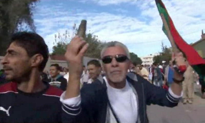 This image made from video shows a protester holding up spent ammunition in Tripoli, Libya after militiamen attacked peaceful protesters demanding the disbanding of the country's rampant armed groups on Friday, Nov. 15, 2013, killing tens of people as they opened fire on the march with heavy machine guns and rocket-propelled grenades. (AP Photo via AP video)