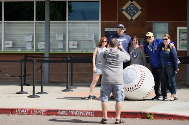 People take photos as closed signs and MLB news releases are displayed on box office windows outside of Peoria Stadium in Peoria, Arizona, where the Seattle Mariners have their Spring Training headquarters (AFP Photo/Christian Petersen)