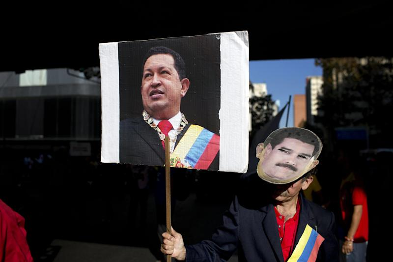 FILE.- In this Tuesday, Feb. 25, 2014 photo a worker from the National Telecommunications Company CANTV holds a sign of Venezuela's former President Hugo Chavez and wears a mask of current President Nicolas Maduro during a rally to show support for the government in Caracas, Venezuela. Heartfelt devotion is a crucial but fading force for Chavez's hand-picked successor, President Nicolas Maduro. Despite daily invocations of his mentor, and control of the powerful party apparatus he inherited, Maduro is increasingly on his own in a fight against a destabilizing wave of anti-government protests.(AP Photo/Rodrigo Abd, File)