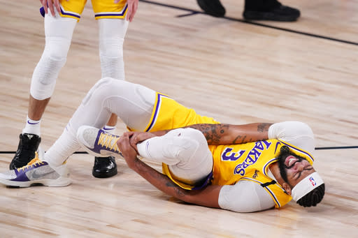 Los Angeles Lakers' Anthony Davis (3) grabs his ankle after a fall during the second half of an NBA conference final playoff basketball game against the Denver Nuggets Thursday, Sept. 24, 2020, in Lake Buena Vista, Fla. (AP Photo/Mark J. Terrill)