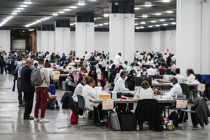 Poll workers count absentee ballots for the city of Detroit at the TCF Center on Nov. 3.