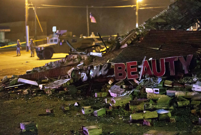 <p>Missouri National Guard stand watch in the background at the scene where a beauty salon was burned to the ground in the riots following Monday's grand jury announcement, Nov. 26, 2014, in Ferguson, Mo. (AP Photo/David Goldman) </p>