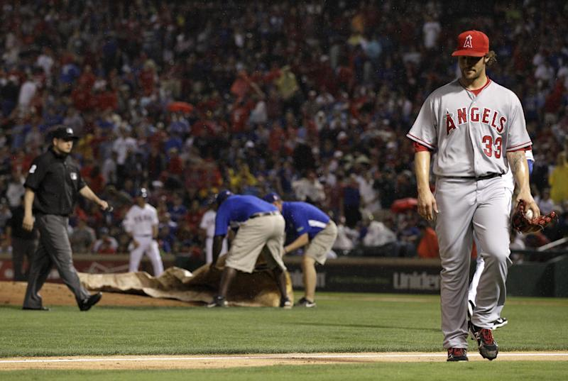 Los Angeles Angels' C.J. Wilson (33) walks off the field as the Texas Rangers grounds crew place the tarp over the mound after the baseball game was delayed due to rain in the first inning on Friday, May 11, 2012, in Arlington, Texas. (AP Photo/Tony Gutierrez)