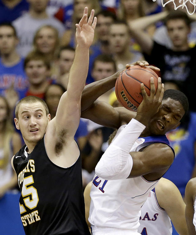 Kansas' Joel Embiid beats Fort Hays State's Marty Wendel to a rebound during the first half of an exhibition NCAA college basketball game Tuesday, Nov. 5, 2013, in Lawrence, Kan. (AP Photo/Charlie Riedel)