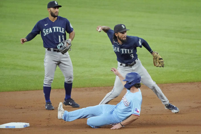 Seattle Mariners shortstop J.P. Crawford (3) throws to first after forcing out Texas Rangers' Charlie Culberson, bottom, at second base in the first inning of a baseball game Sunday, Aug. 1, 2021, in Arlington, Texas. Mariners second baseman Abraham Toro (13) looks on. (AP Photo/Louis DeLuca)