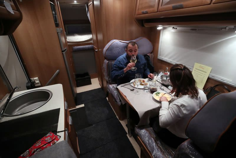 Customers enjoy dinner sitting inside a motorhome camper parked at the Belgian restaurant Matthias And Sea, despite the COVID-19 pandemic lockdown in Tarcienne