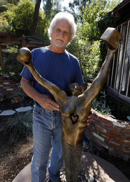 """In this Thursday, Sept. 18, 2012 photo, Tony Dow, actor, director and artist, poses with one of his works at his home and studio in the Topanga area of Los Angeles. When it comes time to sitting down in a studio and carving out bronze and wooden sculptures inspired by the nature all around him, Wally isn't leaving it up to the Beav these days. Dow, who famously played the Beaver's older brother Wally on the classic 1950s-60s sitcom """"Leave it To Beaver,"""" is carving out a name for himself in the art world these days, as an abstract artist. (AP Photo/Reed Saxon)"""