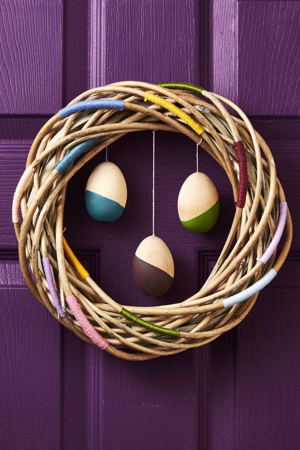 """<p>Spice up an ordinary grapevine wreath by wrapping colorful embroidery thread around branch sections. Add movement to this door decoration with suspended wooden eggs in the center — hot-glue thread to the backs and then tie in place.</p><p><a class=""""link rapid-noclick-resp"""" href=""""https://www.amazon.com/Bulk-Buy-Darice-Grapevine-Wreath/dp/B0033M0HG4?tag=syn-yahoo-20&ascsubtag=%5Bartid%7C10055.g.2217%5Bsrc%7Cyahoo-us"""" rel=""""nofollow noopener"""" target=""""_blank"""" data-ylk=""""slk:BUY GRAPEVINE WREATH"""">BUY GRAPEVINE WREATH</a> <br></p>"""