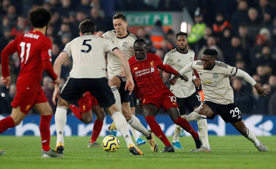 Liverpool's Sadio Mane battles for the ball with Manchester United players.