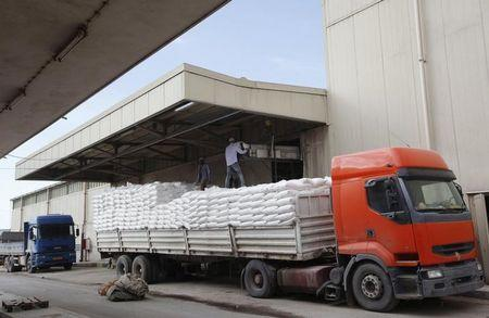 Workers load flour at a mill for Libyan grains in Tripoli