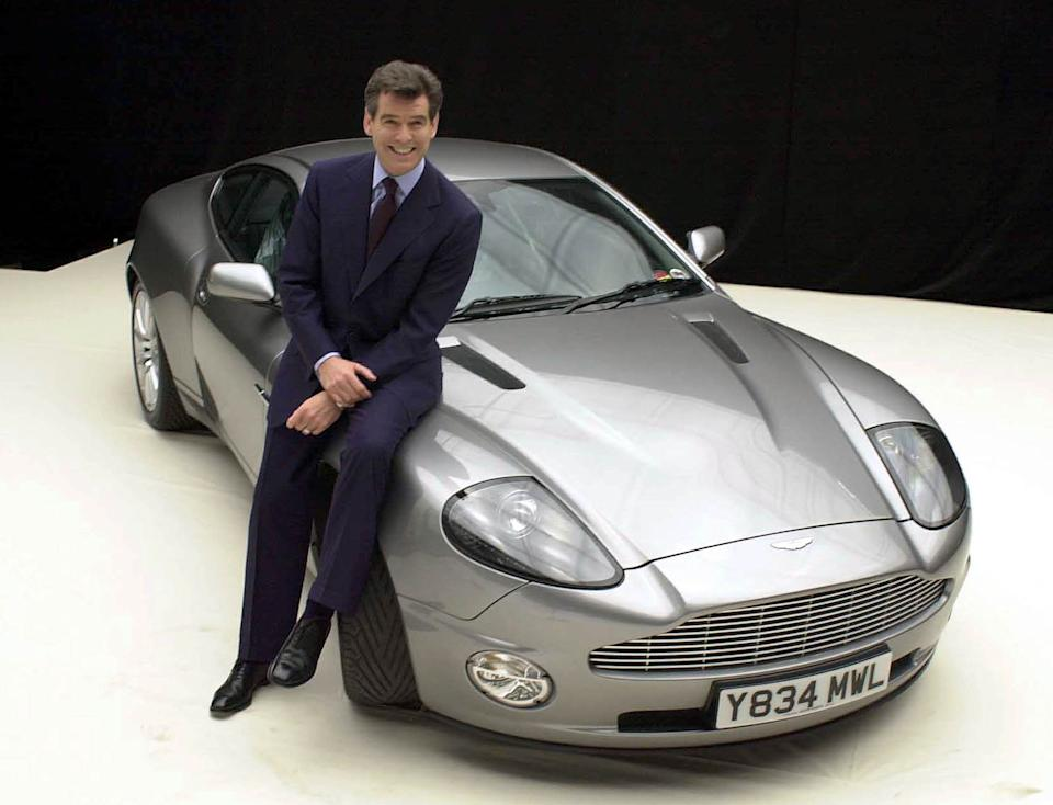 James Bond actor Pierce Brosnan with the Aston Martin Vanquish during a photocall for 'Bond 20', the working title for the latest film which starts production on the at Pinewood Studios in Iver, Bucks.     * 19/11/02: A group of convalescing Bond fans was today being treated to a sneak preview of the latest 007 adventure. Patients at St Thomas  Hospital in London were watching the new action film Die Another Day at a special screening at the UK s only hospital cinema. The showing of the new movie, which goes on general release on Wednesday, was the first preview to be held at MediCinema at the hospital.   (Photo by William Conran - PA Images/PA Images via Getty Images)