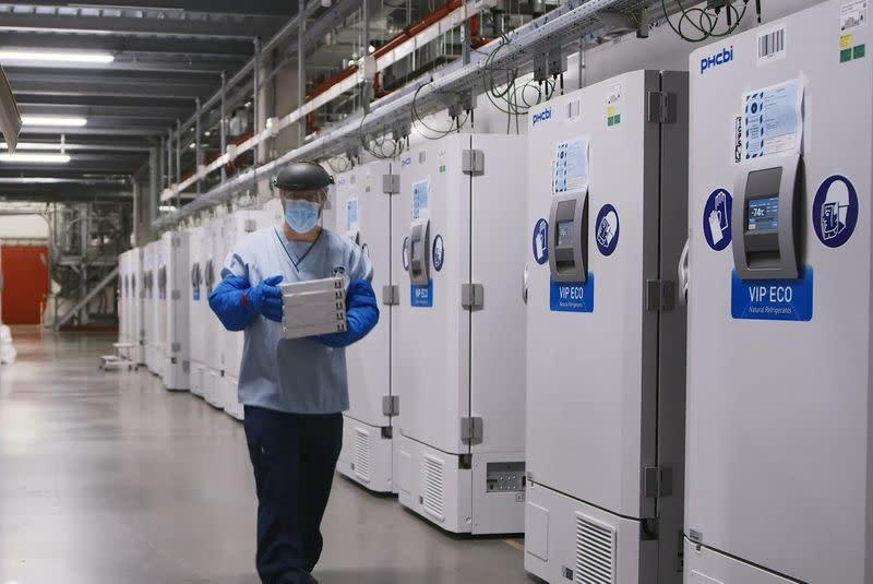 A worker passes a line of freezers holding coronavirus disease (COVID-19) vaccine candidate BNT162b2 at a Pfizer facility in Puurs