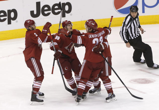 Phoenix Coyotes' Keith Yandle (3), Mikkel Boedker (89), Oliver Ekman-Larsson (23) and Shane Doan, rear, celebrate a go-ahead goal against the Calgary Flames during the third period of an NHL hockey game, Saturday, March 15, 2014, in Glendale, Ariz. The Coyotes won 3-2. (AP Photo/Matt York)