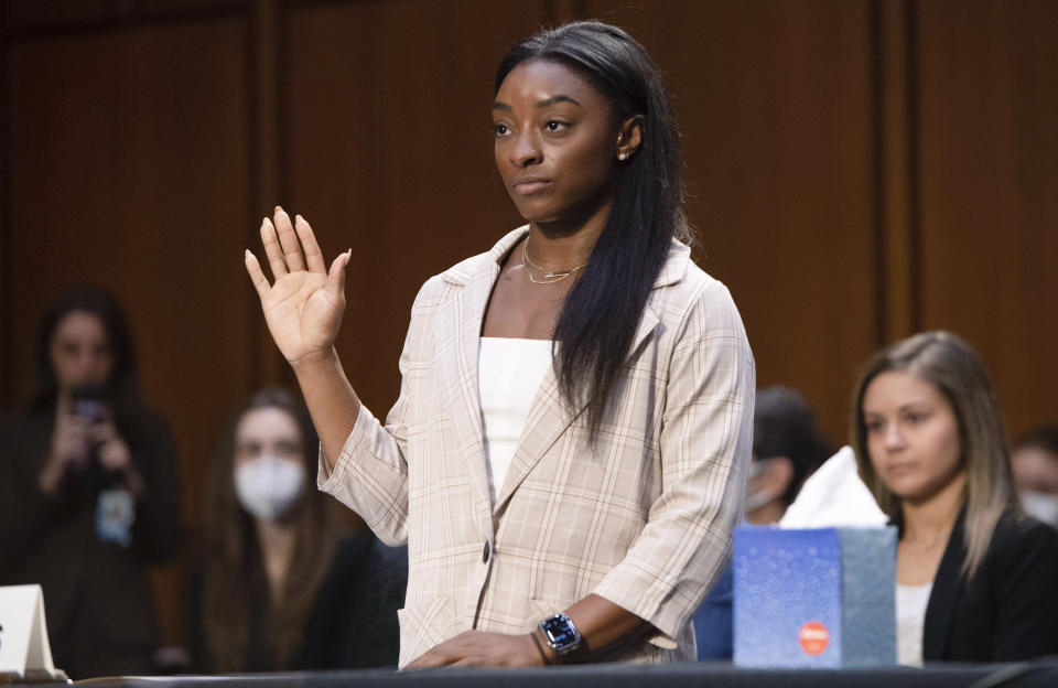 United States Olympic gymnast Simone Biles is sworn in during a Senate Judiciary hearing about the Inspector General's report on the FBI's handling of the Larry Nassar investigation on Capitol Hill, Wednesday, Sept. 15, 2021, in Washington. Nassar was charged in 2016 with federal child pornography offenses and sexual abuse charges in Michigan. He is now serving decades in prison after hundreds of girls and women said he sexually abused them under the guise of medical treatment when he worked for Michigan State and Indiana-based USA Gymnastics, which trains Olympians. (Saul Loeb/Pool via AP)