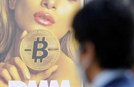 FILE PHOTO: A man stands near an advertisement of a cryptocurrency exchange in Tokyo, Japan March 30, 2018. Picture taken March 30, 2018.  REUTERS/Toru Hanai