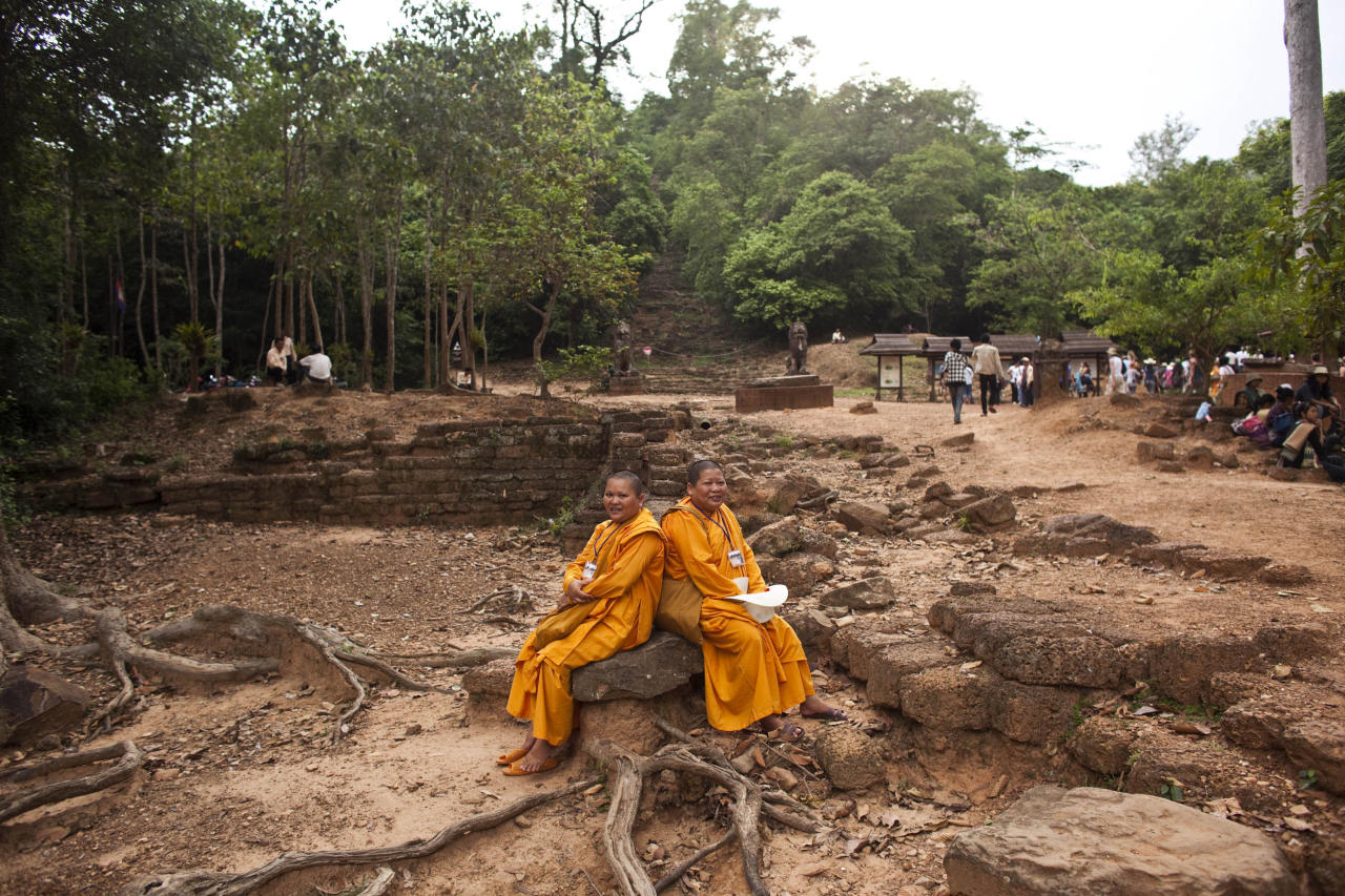 In this photo taken on May 11, 2011, Buddhist monks and western tourist gather at the bottom of the 10th century temple Bakheng in the Angkor Wat complex near Siem Reap, Cambodia. Cambodian Tourism Minister Thong Khon says some 6 million visitors per year are projected by 2020. (AP Photo/David Longstreath)
