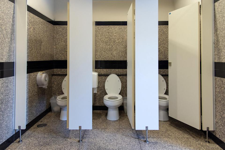 Public bathroom with three stalls with open doors