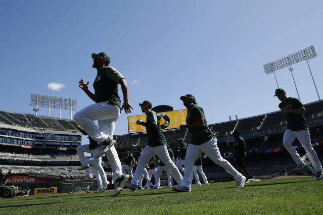 Oakland Athletics players warm up during baseball practice in Oakland, Calif., Tuesday, Oct. 1, 2019. The Athletics are scheduled to face the Tampa Bay Rays in an American League wild-card game Wednesday, Oct. 2. (AP Photo/Jeff Chiu)