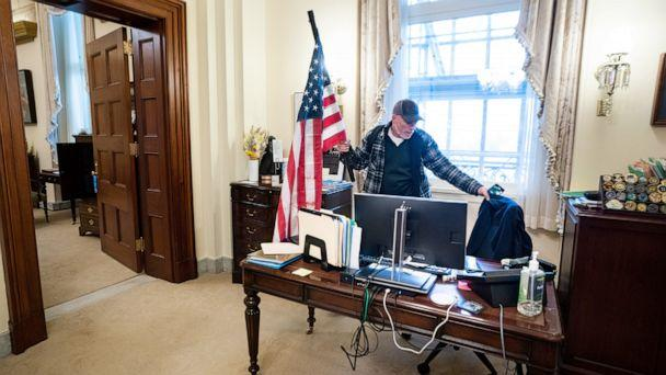 PHOTO: Richard Bigo Barnett takes a seat in the office of Speaker of the House Nancy Pelosi after breaching Capitol security during a protest against Congress certifying Joe Biden as the next president in Washington, Jan 6, 2021. (Jim Lo Scalzo/EPA via Shutterstock)